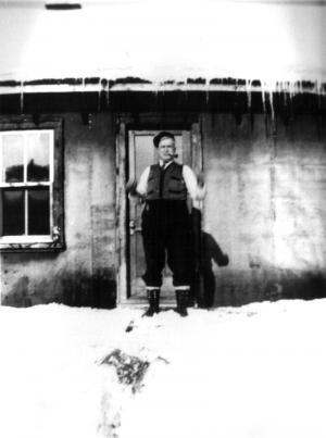 Un homme fumant la pipe devant un camp