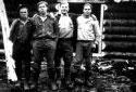 Quatre travailleurs forestiers devant un camp