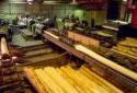 Trois travailleurs surveillent les écorceuses dans l'atelier de sciage Fraser de  Plaster Rock