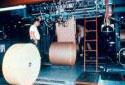 Deux travailleurs procédant à l'emballage de rouleaux de papier bond